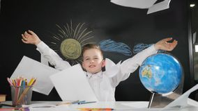 czarnych tła pojęcia do copyspace książek Śliczny boyl siedzi przy biurkiem z blackboard za ona Szczęśliwi uczniowscy rzuty papie zbiory