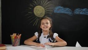 czarnych tła pojęcia do copyspace książek Atrakcyjna dziewczyna siedzi przy biurkiem z blackboard za ona Szczęśliwi uczennica rzu zdjęcie wideo