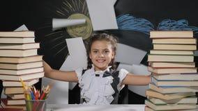 czarnych tła pojęcia do copyspace książek Atrakcyjna dziewczyna siedzi przy biurkiem z blackboard za ona Szczęśliwi uczennica rzu zbiory wideo