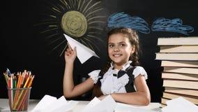 czarnych tła pojęcia do copyspace książek Atrakcyjna dziewczyna siedzi z papieru samolotem w ręce Biurko i blackboard za one Ucze zbiory
