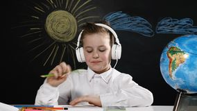 czarnych tła pojęcia do copyspace książek black tła pojedynczy kciuk, Śliczna chłopiec siedzi przy biurkiem z kulą ziemską na nim zbiory