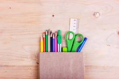 czarnych t?a poj?cia do copyspace ksi??ek Barwioni ołówki, nożyce, władca, kompasy w brąz papierowej torbie zdjęcie stock