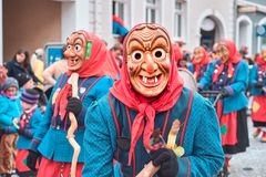 Czarodziejska czarownica w czerwonych i błękitnych kostiumowych spojrzeniach śmiesznych Uliczny karnawał w południowym Niemcy - C fotografia stock