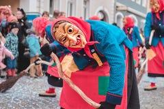 Czarodziejska czarownica w czerwonym błękitnym kostiumu z przegiętą postawą Uliczny karnawał w południowym Niemcy - Czarny las obraz stock