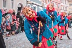 Czarodziejska czarownica w czerwonym i błękitnym kostiumu z przegiętą postawą Uliczny karnawał w południowym Niemcy - Czarny las fotografia stock