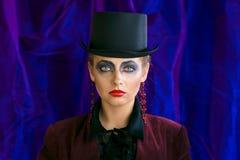 Czarodziejska teatralnie sztuka makijażu dziewczyna w kapeluszowej butli na purpurowym tle Zdjęcie Stock