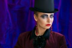 Czarodziejska teatralnie sztuka makijażu dziewczyna w kapeluszowej butli na purpurowym tle Zdjęcie Royalty Free