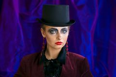Czarodziejska teatralnie sztuka makijażu dziewczyna w kapeluszowej butli na purpurowym tle Zdjęcia Stock