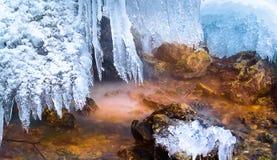 Czarodziejski strumień z barwionymi kamieniami i obwieszenie soplami, tęcza Spada, Rosja zdjęcie royalty free