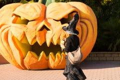 Czarownicy odprowadzenie blisko pomarańczowej Halloween bani zdjęcia stock