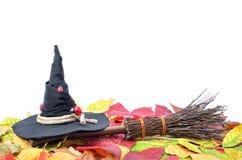 Czarownicy ` s kapelusz i miotła na jesień liściach Obrazy Stock