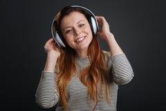 Czarująca uśmiechnięta dziewczyna słucha muzyka Zdjęcie Stock