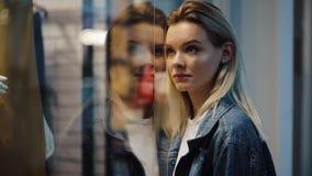 Czarujący młodzi blondynki kobiety stojaki przed przedstawienia okno w zakupy centrum handlowym zbiory wideo