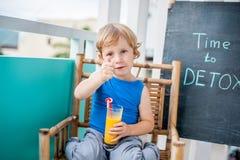 CZAS DETOX kredy inskrypcja Chłopiec jest pić świeży, zdrowy, detox napój robić od owoc Owocowy potrząśnięcie, świeży sok, mleko Obraz Royalty Free