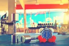 Czas dla ćwiczyć budzika i dumbbell Gym tło Część czasu Zdrowy pojęcie Fotografia Royalty Free