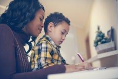 Czas dla kształcić Amerykanin Afrykańskiego Pochodzenia chłopiec pisze w domu z cześć zdjęcie stock