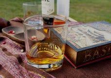 Czas dla napoju - szkło whisky na stole z książką, butelką i drewnianym pucharem, Obrazy Royalty Free