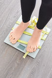 Czas gubić kilo z kobieta ciekami kroczy na ciężar skala Fotografia Royalty Free