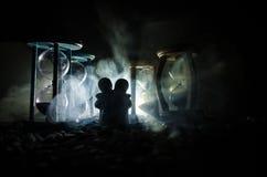 czas i miłości pojęcie Sylwetki zabawkarskie ceramiczne postacie ściska między hourglasses w zmroku zaświecali tło z mgłą Zdjęcie Stock