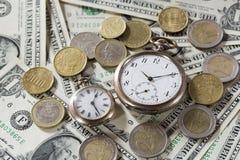 Czas jest pieniądze finansowym pojęciem z starymi roczników zegarami, dolarowymi rachunkami i euro monetami, Zdjęcia Stock