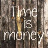 Czas jest pieniądze ręcznie pisany z biel kredą na drewnianym tle Zdjęcie Royalty Free