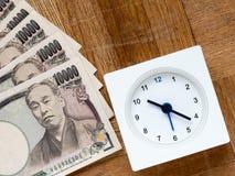 Czas jest pieniądze, zegarem i japończykiem, 10000 jenów rachunków na drewnianym Zdjęcie Royalty Free