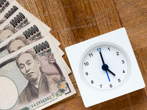 Czas jest pieniądze, zegarem i japończykiem, 10000 jenów rachunków na drewnianym Zdjęcia Stock