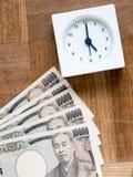 Czas jest pieniądze, zegarem i japończykiem, 10000 jenów rachunków na drewnianym Zdjęcie Stock