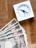 Czas jest pieniądze, zegarem i japończykiem, 10000 jenów rachunków na drewnianym Fotografia Stock