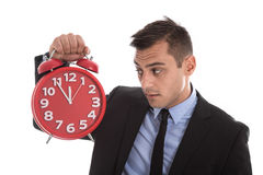 Czas jest pieniądze: biznesmen trzyma up czerwonego budzika odizolowywający Obrazy Royalty Free