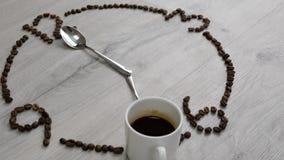 Czas target375_0_ kawę Zegarek tarcza kawowe fasole rozkłada na drewnianym stole filiżanka kawy zamiast 7 łyżek i godziny zbiory