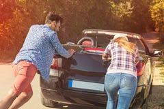 Czas wolny, wycieczka samochodowa, podróż i ludzie pojęć, - szczęśliwi przyjaciele pcha łamającego kabrioletu samochód wzdłuż wie Zdjęcia Royalty Free