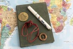 Czasopismo z piórem, talizmanem i monetą na mapie, Fotografia Stock