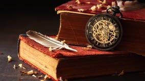 Czasu upływ meandruje kieszeniowego zegarek na starych książkach z piórkami i suszącymi kwiatów płatkami zbiory
