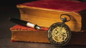 Czasu upływ meandruje kieszeniowego zegarek umieszczającego obok starej książki i pióra na książce zbiory wideo