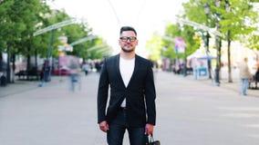 Czasu upływ atrakcyjny brodaty mężczyzna z teczki pozycją w uliczny samotnym zbiory wideo