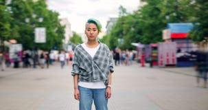 Czasu upływ piękny Azjatycki nastoletni z farbującą włosianą patrzeje kamerą outdoors zbiory wideo