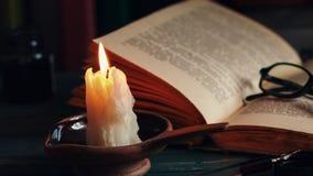 Czasu upływu świeczka i stare książki przy nighttime Zamyka w górę widok Filmowy koloru oceniać zbiory
