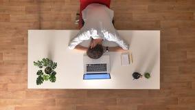 Czasu upływu klamerka niezobowiązująco ubierający biznesowy mężczyzna śpi na biurku przed jego laptopem w lekkim drewnianym biurz zdjęcie wideo