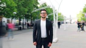 Czasu upływu portret poważny facet stoi w ulicie na letnim dniu w szkłach zbiory wideo