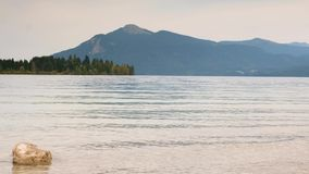 Czasu upływu wideo kamień w wodzie halny jezioro Delikatne fala na jesieni jeziorze, lasowych wyspach i górach w tle, zdjęcie wideo
