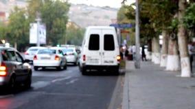 Czasu upływu zamazujący pojazdy, zamazujący ludzie krzyżują drogę, przeciw tłu zieleni drzewa zdjęcie wideo