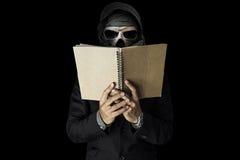 Czaszka facet w czarnego kostiumu czytelniczym notatniku na czarnym ciemnym środowiska tle, Zdjęcie Stock