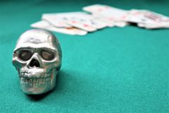 Czaszka, pokład karty na zielonym stole Kasyno stół obrazy royalty free