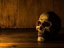 Czaszka umieszcza na drewnianym stole Tło jest drewnianym światłem od świeczki i talerzem czaszka Fotografia Royalty Free