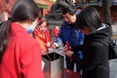 Czciciele trzyma kadzidłowych kije one modlą się przy Yonghegong Lama świątynią w Pekin Fotografia Royalty Free