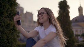 Cześć tam! Młoda dziewczyna macha ekran jej chłopak in camera podczas gdy mieć wideo wezwanie w wiosna parku zbiory wideo