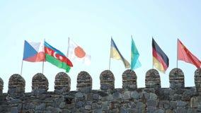 Czech Azerbaijani Japanese Ukrainian Kazakh German Chinese Flags on fortress wall. Flags on fortress wall tower Czech Azerbaijani Japanese Ukrainian Kazakh stock video footage