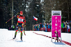Czech biathlete Michal Slesingr passes the finish sign with winning hand gesture du Stock Photo