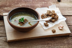 Czech garlic soup with homemade croutons close up in a bowl on the wooden board.  royalty free stock photography